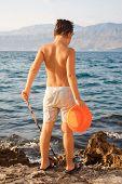 Young boy fishing with bucket on rocks on the island of Brac, Croatia