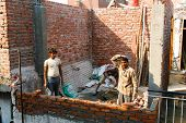 DELHI - FEBRUARY 29: Three men laying a brick wall for a house on February 29, 2008 in Delhi, India. Contributing to India's booming economy.