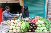 DELHI - JAN 15: Muslim woman with veil shopping vegetables on street stand on January 15, 2008 in De