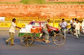 DELHI - SEP 22: Transporting packages through city on bicycle trailer on September 22, 2007 in Delhi, India. Human labor is still cheaper than automated transport.
