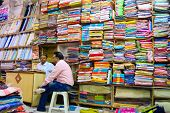 DELHI - DECEMBER 2: Two textile merchants sit in a wholesale shop stacked with fabric on shelves on
