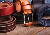 Leather Colored Belts On A Wooden Table. Collection Of Leather Belts On A Wooden Table. poster