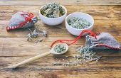 Homemade Sachets With Wormwood, Two White Bowls With Dry Herbs, On Wooden Table Closeup poster