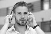 Young Man Listening Music With Headphones On Urban Background, Defocused. Macho With Calm Face Holds poster