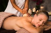 Senior woman feeling relaxed after ayurvedic back massage in a luxury spa. Masseuse doing pinda mass poster