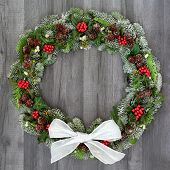 Traditional winter and Christmas natural wreath with bow, holly, snow covered spruce pine fir, mistl poster