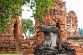 Headless and armless Buddha image sitting in front of pagoda in Ayutthaya, Thailand