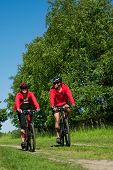 Young couple riding mountain bike in a nature