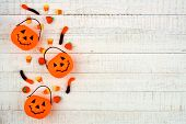 Halloween Side Border With Jack O Lantern Pails And Spilling Candy. Above View On A White Wood Backg poster