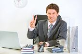 Smiling Modern Businessman Sitting At Office Desk And Showing Victory Gesture