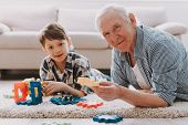 Portrait Grandpa And Grandson Playing With Toys. Family Relationship Between Grandfather And Grandso poster