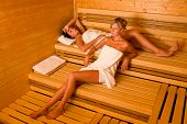 Sauna two healthy beautiful women relaxing lying wrapped in towel