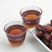 Two cups of black tea with a bowl of ripped dates.
