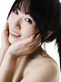 Closeup of a beautiful Chinese woman with smooth, clear skin, looking into the camera and holding he