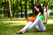 woman sitting on ground and reading book