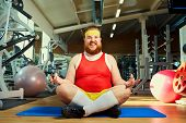 Funny Fat Man With A Beard Doing Yoga In The Gym poster