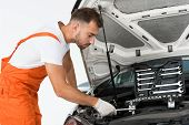 Side View Of Handsome Auto Mechanic Auto Mechanic Fixing Car With Wrench On White poster