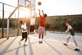 Group of young sporty multiethnic men basketball players playing basketball at the sport ground poster