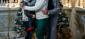 The Family Of Their Four People Hugging Against The Background Of The Christmas Tree. Parents And Tw poster