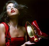 modelo com saco vermelho e sapatos vermelhos. sobre fundo preto.