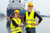Two dockers, a man and a woman, posing in front of a huge cargo ship, moored off at an anchor buoy i