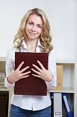 Happy blonde woman standing with application portfolio in the office