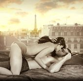 stock photo of love-making  - Young sexy couple making passionate love in bed against window overlooking Paris skyline with retro vintage sepia tones - JPG