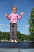 Alegre menina vestida de camiseta rosa pula no trampolim em dia de verão ensolarado