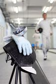 Close up of foil, mask and white glove at background ot going fencer. Shallow DOF.