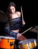 Young woman playing  drum and cymbals in night club.