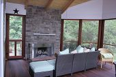 stock photo of screen-porch  - Seating arrangement around a fireplace on a screen porch - JPG