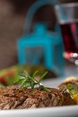 image of flambeau  - closeup of a steak with a rosemary leaf