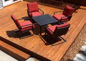 image of red siding  - Backyard deck design with furniture on freshly stained deck - JPG