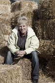 Middle Aged Woman sitting on Straw Bales