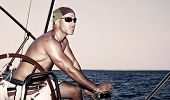 Handsome strong man working on sail boat, sailor enjoys crew duty, luxury lifestyle, yachting sport,