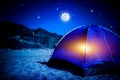 Camp on sandy beach, tent at the night with light inside, moon light, active tourism, hiking and traveling concept