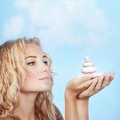 Closeup retrato da menina loira e bonita segurando pedras spa ao ar livre, tratamento de beleza, luxo spa salo