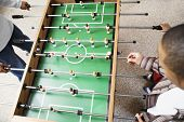 Two boys playing foosball