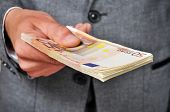 picture of bribery  - a man wearing a suit with a wad of euro bills in his hand - JPG