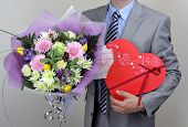 Businessman holding a bouquet of flowers and a red heart shape box of chocolates