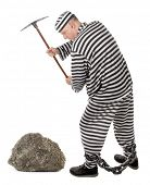 stock photo of prison uniform  - Convict prisoner jailbird pestle rock with pickax - JPG
