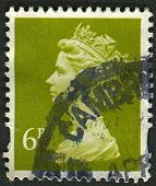 UK-CIRCA 1991: A stamp printed in UK shows image of Elizabeth II is the constitutional monarch of 16 sovereign states known as the Commonwealth realms, in Yellow Olive, circa 1991.