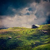 Serenity serene lonely scenery background concept - old house in hills in mountins on alpine meadow in clouds. VIntage style cross process, grain and texture added