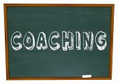 The word Coaching on a blackboard or chalkboard to symbolize learning, team skills and motivation fr
