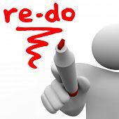 A man with a marker or pen writes the word Re-Do to illustrate a need to revise, change or improve t