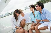 Happy group of friends having fun sailing on a boat