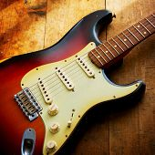 Sunburst color double cutaway electric solid body guitar, on a grungy wooden surface
