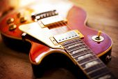 Red sunburst color single cutaway electric solid body guitar, on a old grungy wooden surface. Shallow depth of field.
