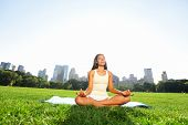 Meditating woman in meditation in New York City Central Park in yoga pose. Girl relaxing with serene