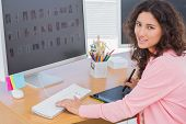 Editor using graphics tablet to edit and smiling at her desk in office